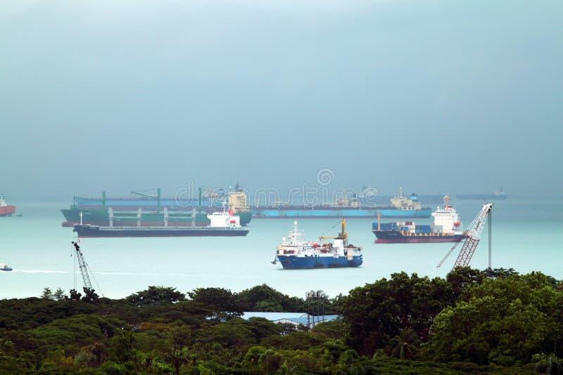 Landskap från fågelsikt av lastfartyg som skriver in en av de mest upptagna portarna i världen, Singapore arkivbilder