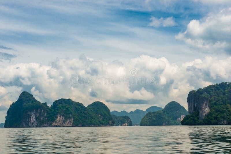 Landskap - havet, gräsplan vaggar och härliga moln i en tropi royaltyfri fotografi