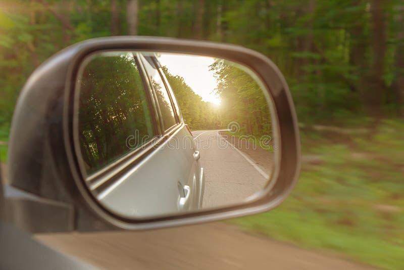 Landskap i sideviewspegeln av en bil, p? v?gbygd Solen ?r gl?nsande arkivbilder