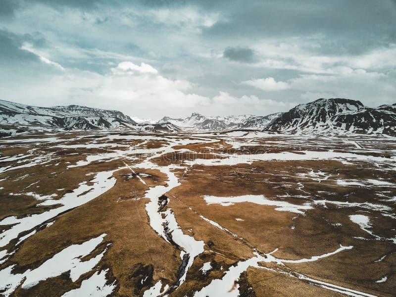 Landskap Island för flyg- sikt med snö och moln, gata och gult och grönt gräs royaltyfria foton