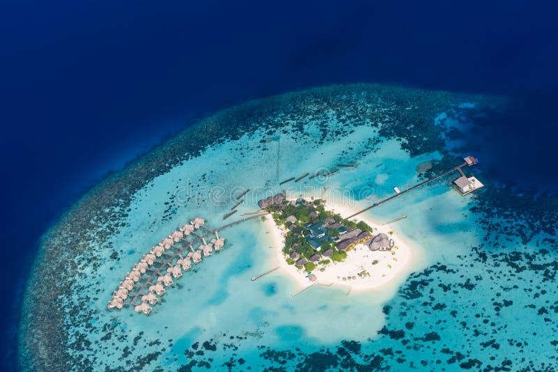 Landskap Maldiverna för flyg- sikt Korallrev och blåtthav med vita sandiga östrand- och lyxvillor royaltyfri bild