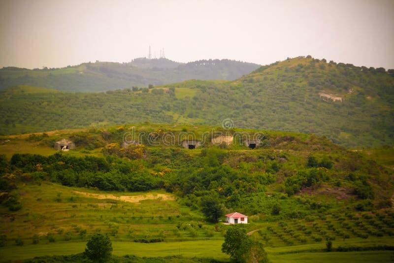 Landskap med de militära bunkerna i mitt av lantliga fält, Apollonia, Fier, Albanien arkivbilder