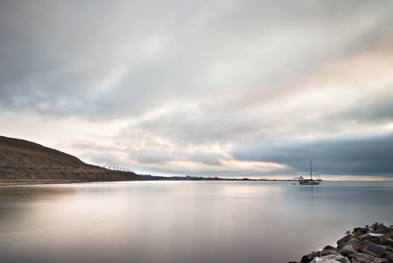 Landskap med en segelbåt och ett berg med gamla kabelbilar på porten av Longyearbyen, Svalbard fotografering för bildbyråer