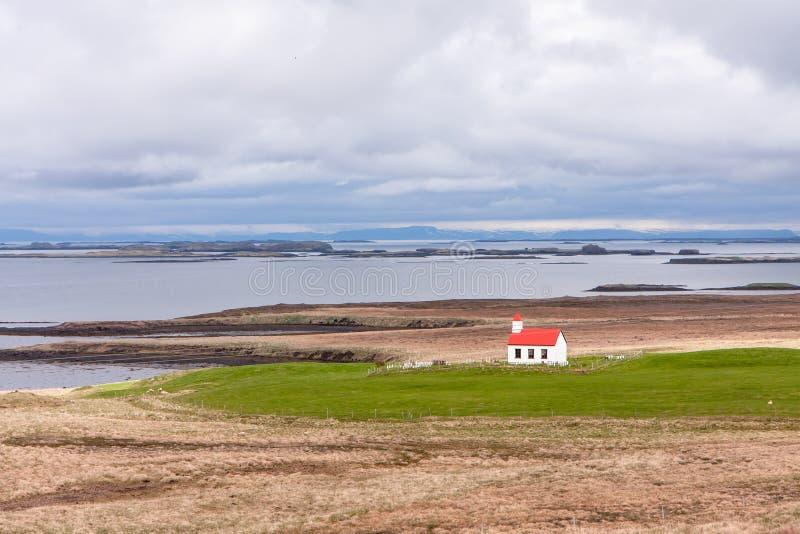Landskap med en sikt av huset vid havfjärden, berget och himlen arkivfoto