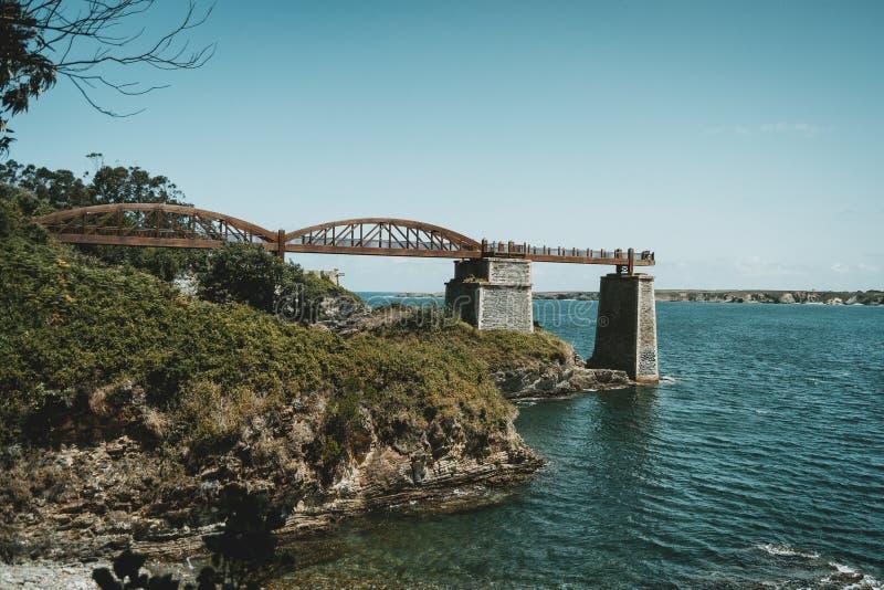 Landskap med en träbro över havet i ribadeo, Spanien arkivbilder