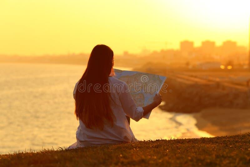 Landskap med en turist- läsning en översikt på solnedgången royaltyfria foton