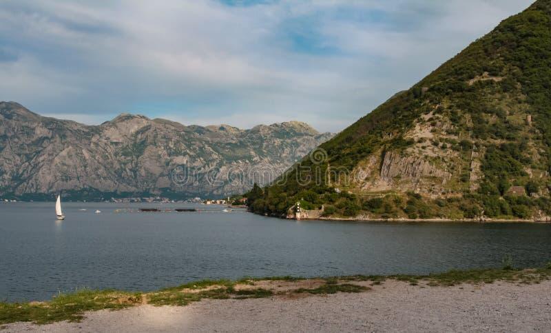Landskap med en yacht på fjärden av Kotor royaltyfria bilder
