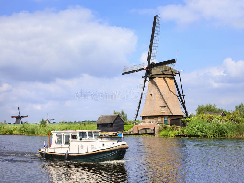 Landskap med ett litet fartyg och en forntida väderkvarn, Kinderdijk, Nederländerna fotografering för bildbyråer