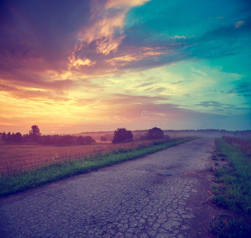 Landskap med fält- och landsvägen på solnedgången royaltyfri foto