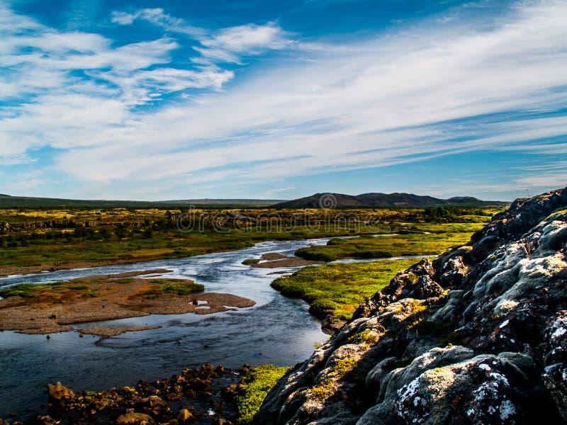 Landskap med floder, blå himmel med moln, gröna växter och kullar i Island arkivbild