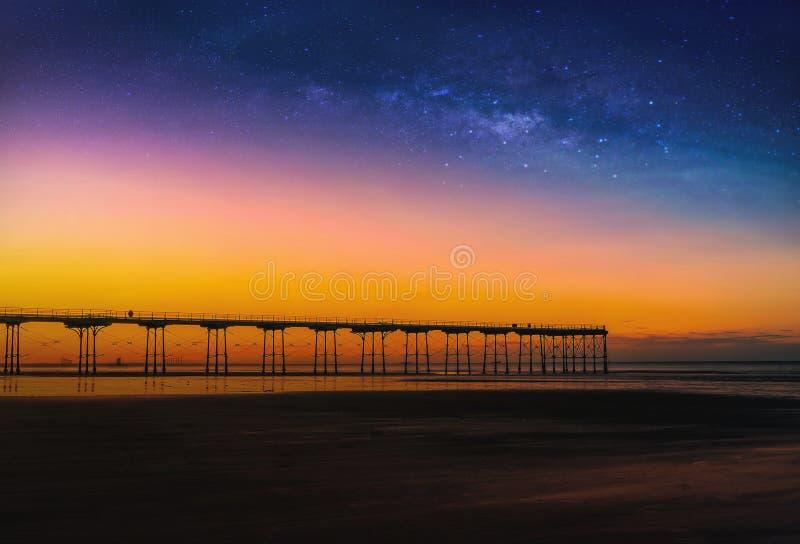 Landskap med galaxen för mjölkaktig väg och solnedgång över pir på Saltburn royaltyfria foton