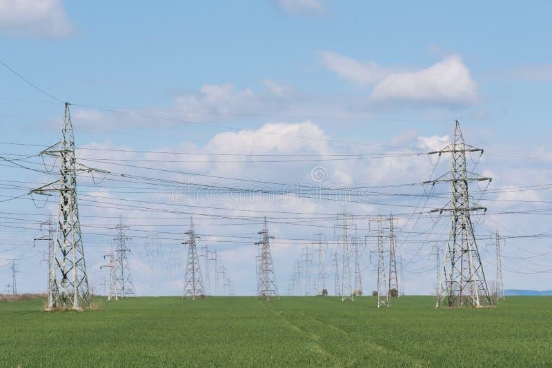 Landskap med hög-spänning kraftledningar Elektricitetsdistributio royaltyfri foto