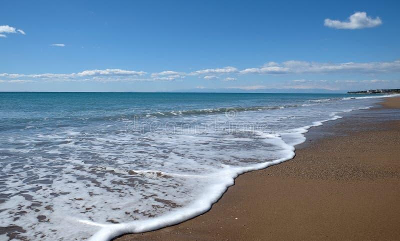 Landskap med havet, bränning, den sandiga stranden och höga berg på långt arkivfoto