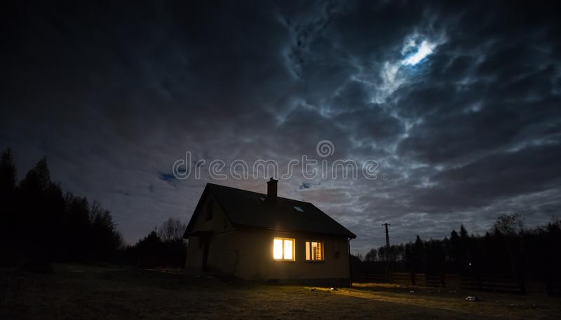 Landskap med huset på natten under molnig himmel arkivfoton