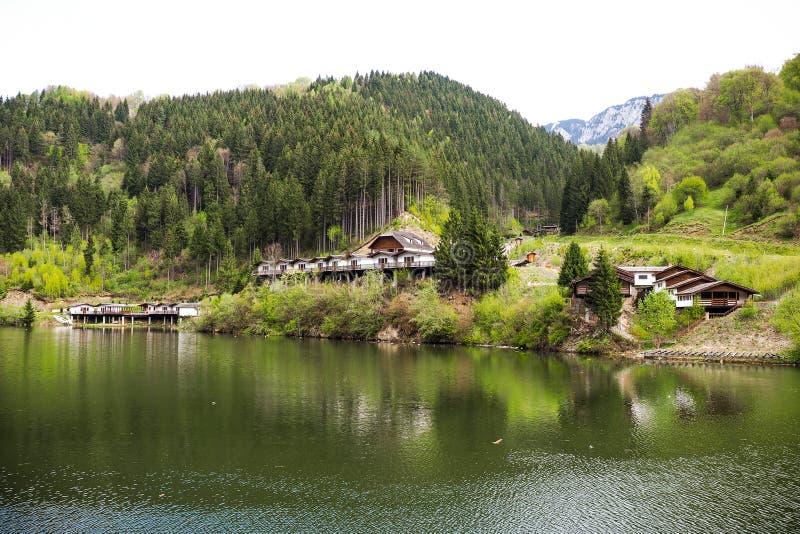 Landskap med kabiner nära en bergsjö arkivfoton