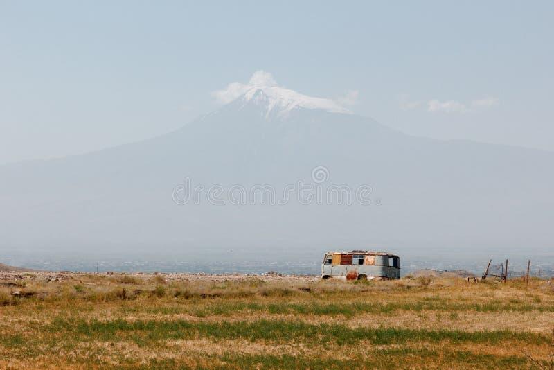 landskap med Mount Ararat och en gammal rostig övergiven buss royaltyfri fotografi