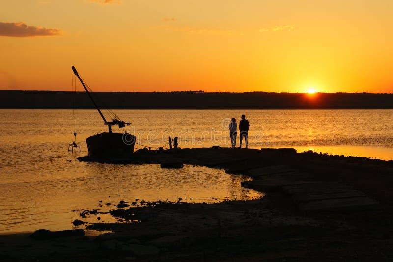 Landskap med vatten, det gamla fartyget och parkonturn på solnedgången fotografering för bildbyråer