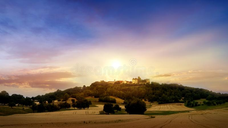 Landskap på solnedgången guld- over solnedgång för lantgårdfält royaltyfri bild