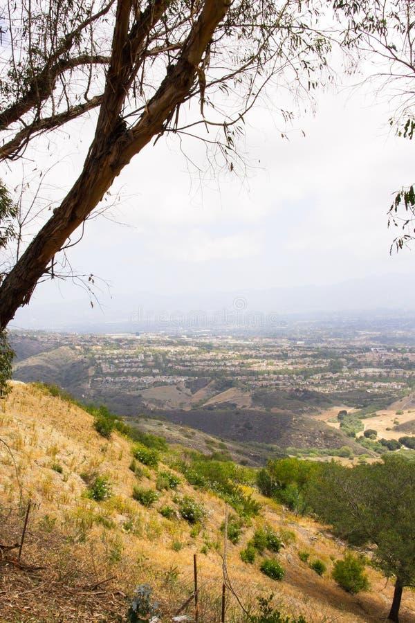 Landskap sikten av det omgeende området uppifrån av kullen som förbiser en cityscape i avståndet royaltyfri foto
