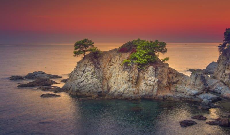 Landskap vaggar och berget på kustlinjen i medelhavet på soluppgång Seascape av spanjorstranden på gryning arkivfoto