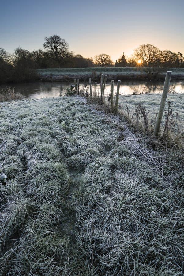 Landskap vintersurnise av floden och frostiga fält fotografering för bildbyråer