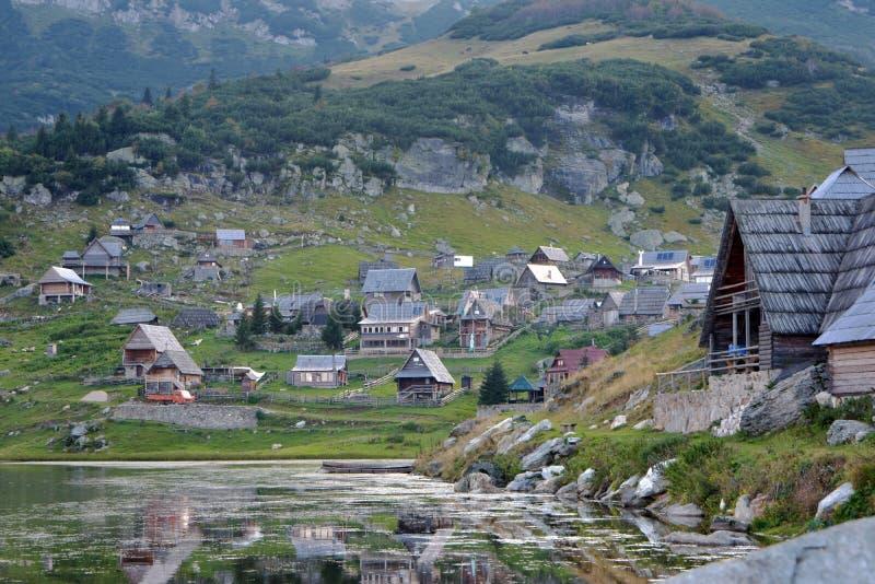 Landskapbild av bergsjöbyn med träkabiner arkivfoton