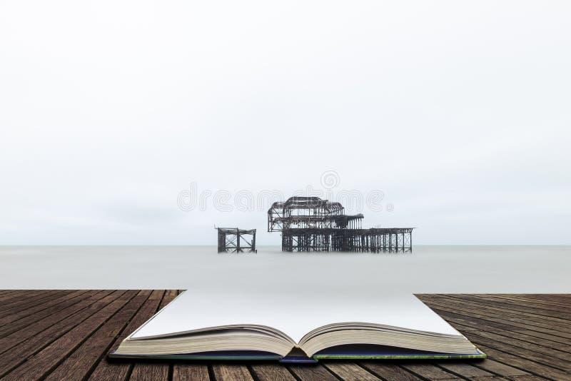 Landskapbild av den övergivna viktorianska västra pir på Brighton i västra Sussex i sidor av den öppna boken, begrepp för berätta royaltyfria bilder