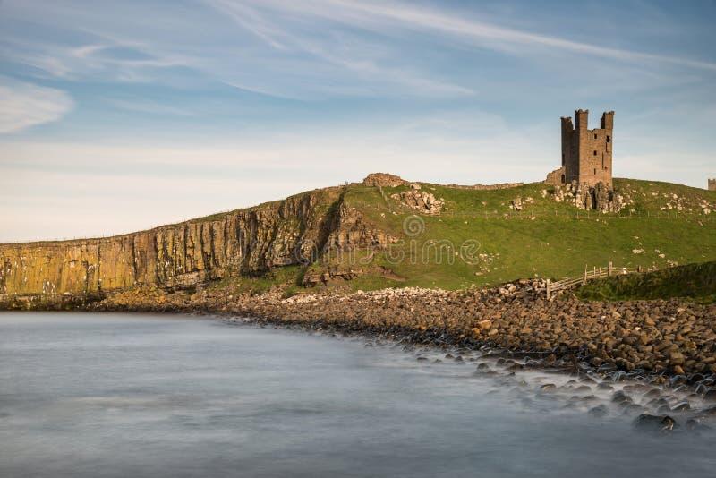 Landskapbild av den Dunstanburgh slotten på den Northumberland coastlien arkivfoto