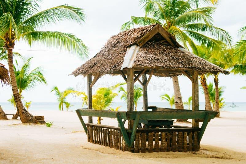 Landskapet av den tropiska ön för paradiset med gömma i handflatan stugor och vitsandstranden royaltyfri foto