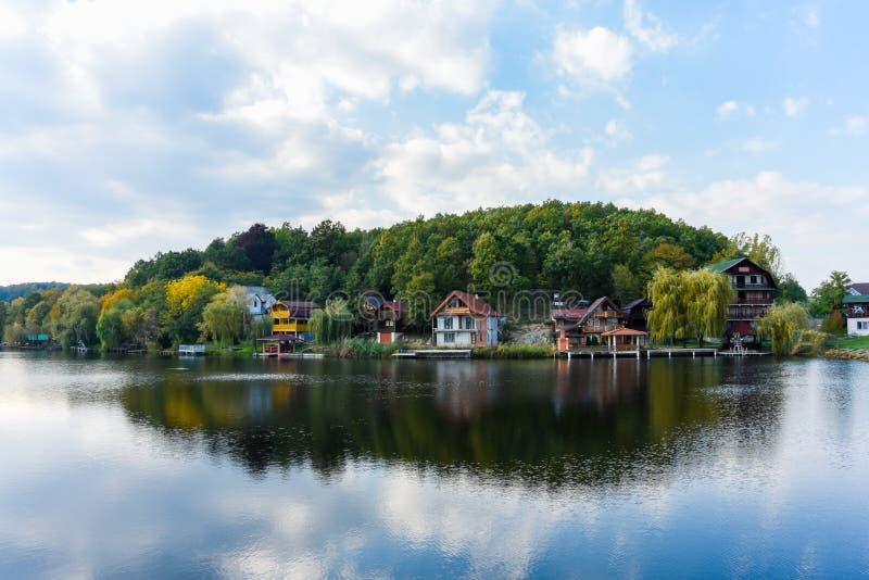Landskapet av hus och träd reflekterade i vattnet på Lacul Mu royaltyfria foton