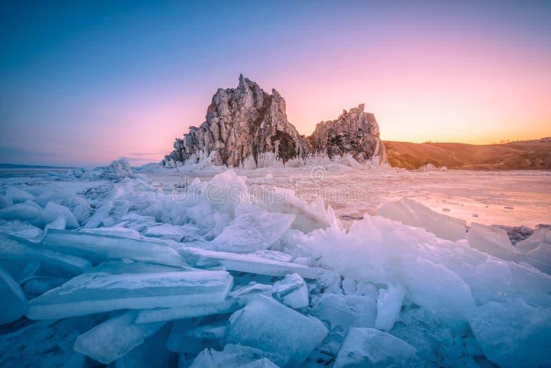 Landskapet av Shamanka vaggar på soluppgång med naturlig brytande is i djupfryst vatten på Lake Baikal, Sibirien, Ryssland arkivbilder