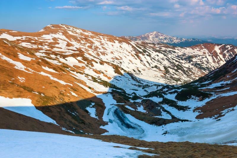 Landskapet av sjön i frosten på de höga bergen och fälten som täckas med snö clouds skyen solig dagfjäder royaltyfri fotografi