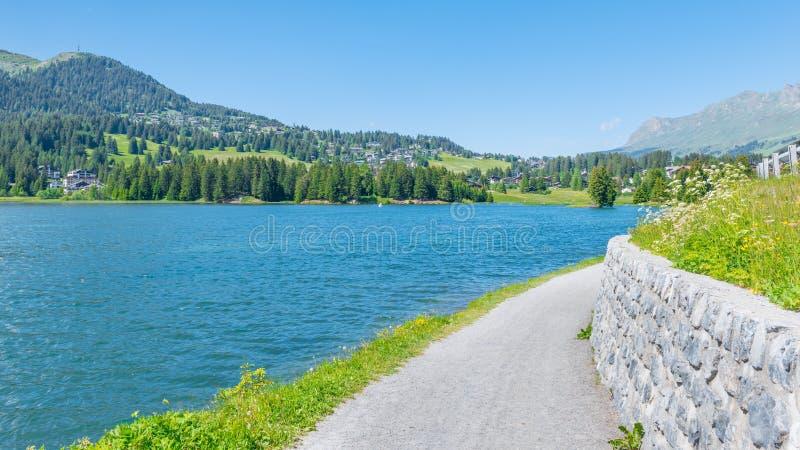 Landskapet i de schweiziska fjällängarna Chalet på kusten av sjön arkivbilder