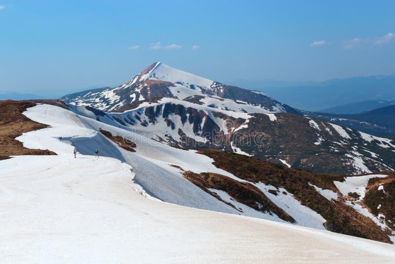 Landskapet med ängarna, de höga bergen och maxima som täckas med snö Stället av turister vilar royaltyfria foton