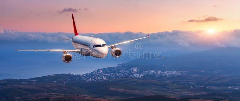 Landskapet med det vita flygplanet flyger i den orange himlen royaltyfri foto