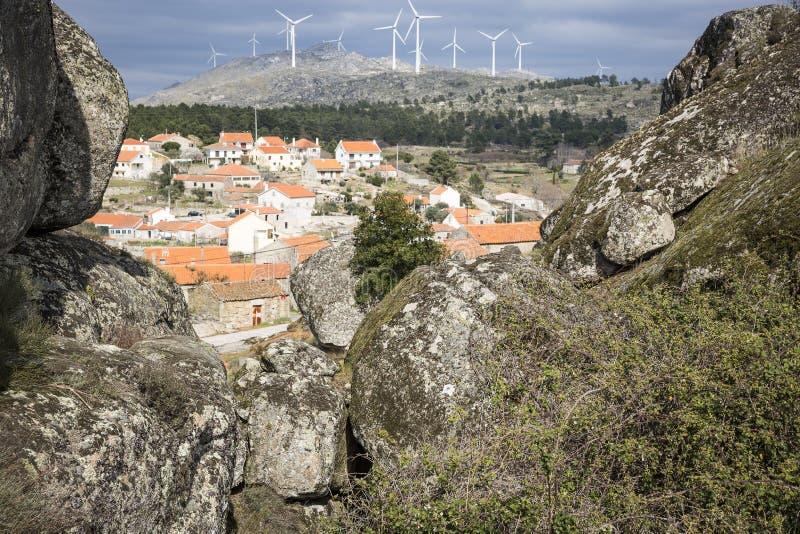 Landskapet med stora stenar, vindturbiner brukar och en sikt över den Sortelha byn royaltyfria foton