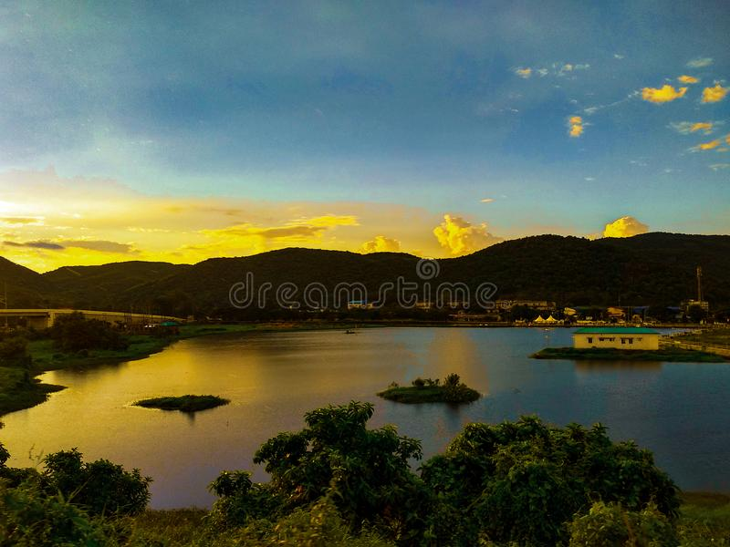 Landskapfoto av solljus som sprider till och med molnen ovanför öppet fält nära en sjö royaltyfria foton