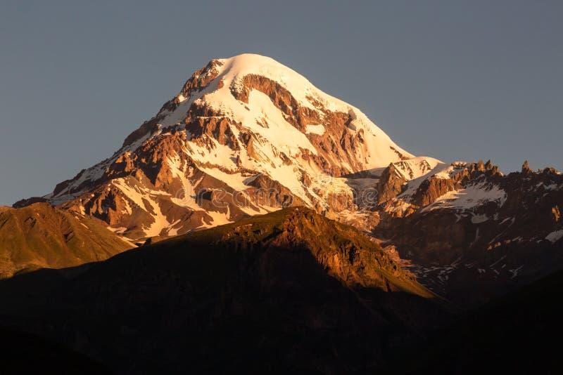 Landskapsikt av berget Kazbeg på soluppgång, Kaukasus berg, land av Georgia royaltyfria bilder