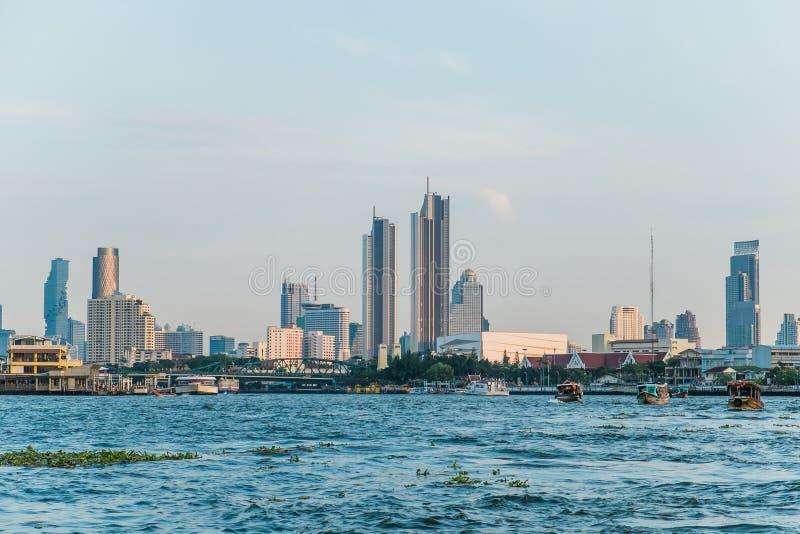 Landskapsikt av byggnader på den Chao Phraya flodstranden och fartygen i floden royaltyfria bilder