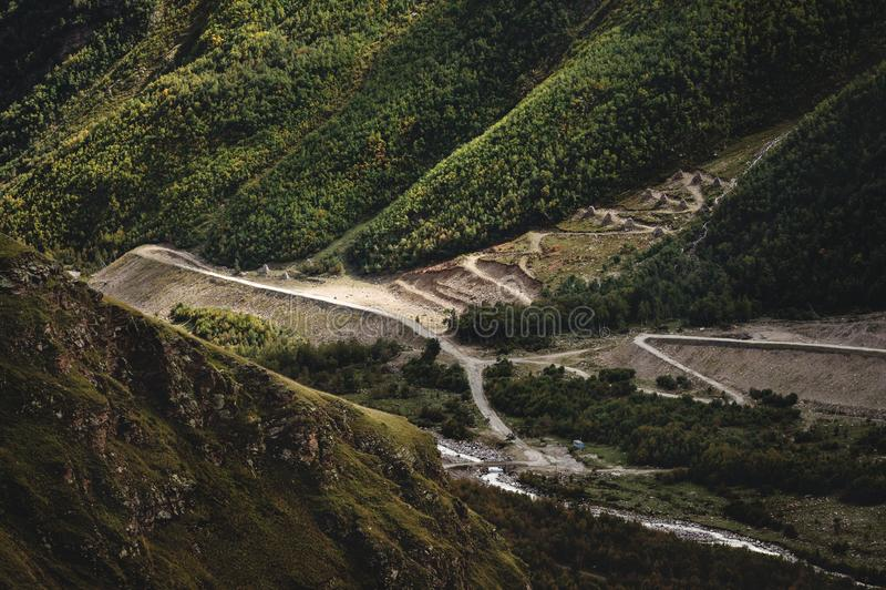 Landskapsikt av den längst ner klyftan som floden flödar av och vägpasserandeen Anti--lavin pyramider in arkivfoton