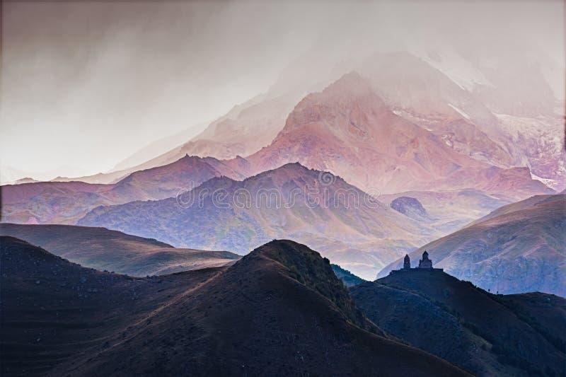 Landskapsikt av den Tsminda Sameba kyrkan i Kazbegi under storm royaltyfria bilder