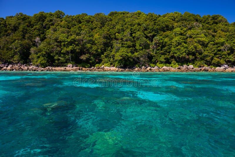 Landskapsikt av havstranden med bergbakgrund under klar himmel royaltyfri bild