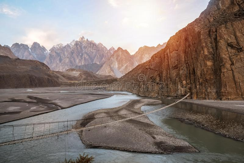 Landskapsikt av Hussaini den hängande bron ovanför den Hunza floden som omges av berg pakistan arkivfoton
