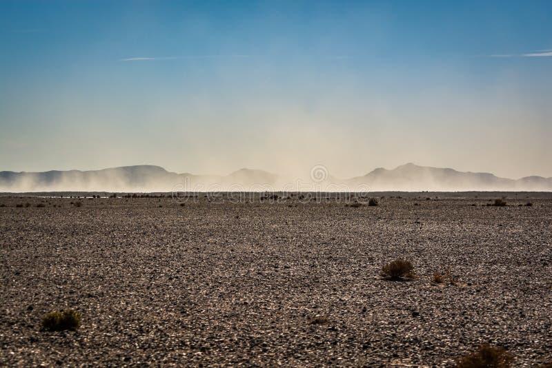 Landskapsikt i öken med berg och liten sandstorm i Marocko arkivbilder