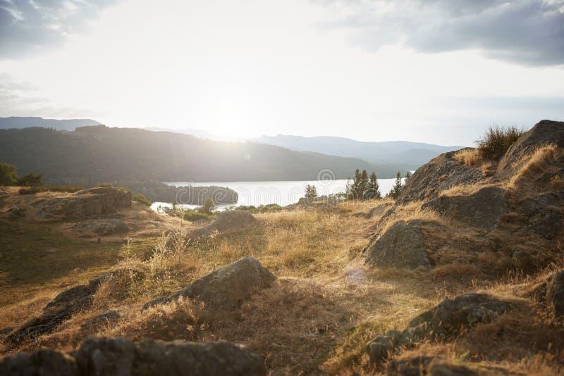 Landskapsikten, berg, fält, vaggar och sjön, inga personer arkivbild