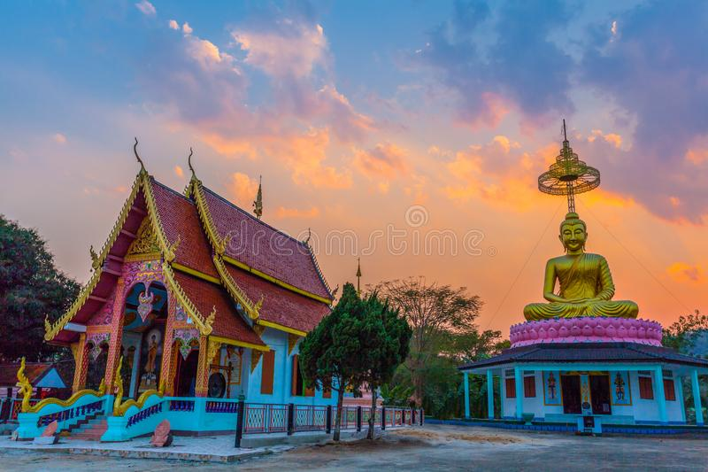 landskapsolnedgång bak den guld- buddhaen i Chiang Rai royaltyfria bilder