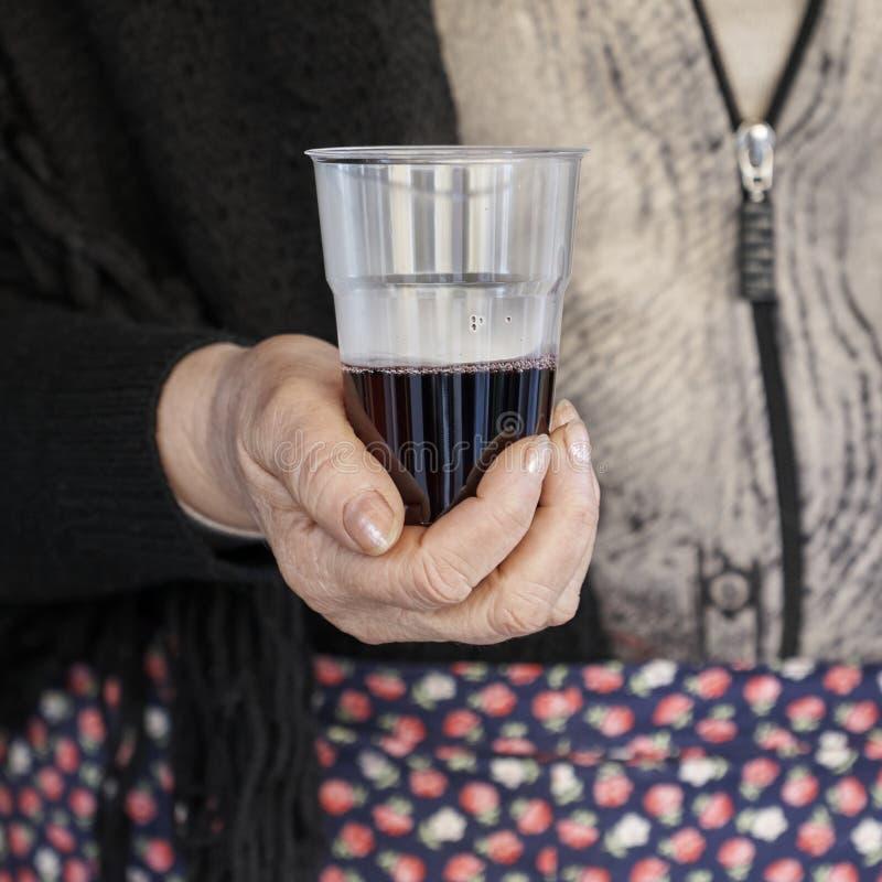 Landsmännin bietet ein Glas Rotwein an stockfoto