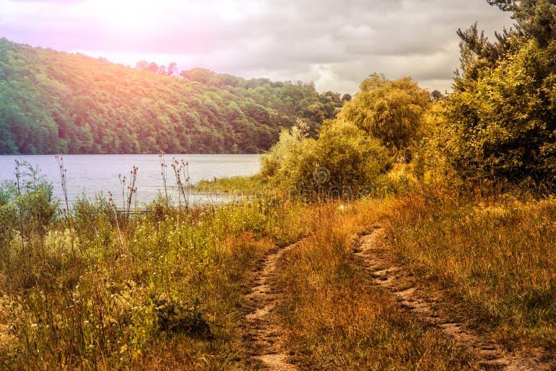 Landstraße in der Wiese Über dem Fluss Feld des grünen Grases gegen einen blauen Himmel mit wispy weißen Wolken stockfoto