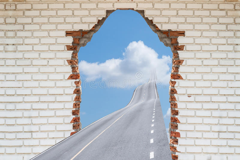 Landstraße, die eine defekte Backsteinmauer durchläuft, stockfotografie