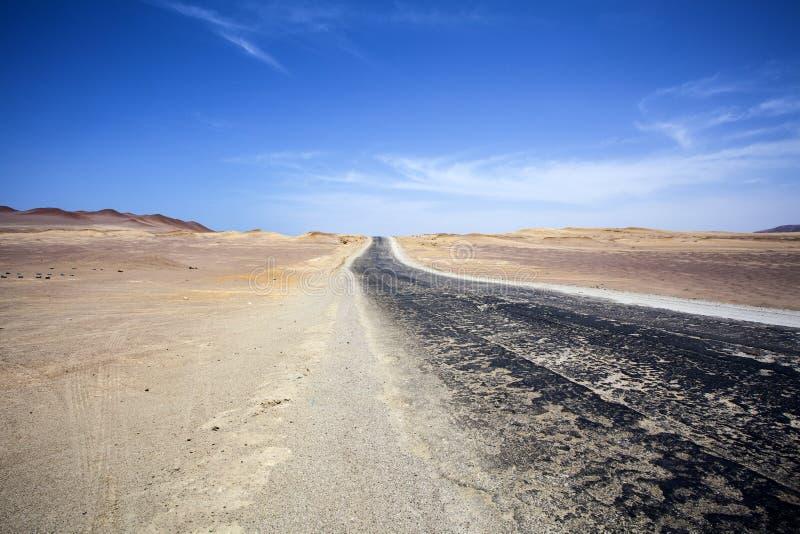Landstraße durch die Wüste nahe bei dem Ozean im Nationalpark Paracas in Ica, Peru stockbild